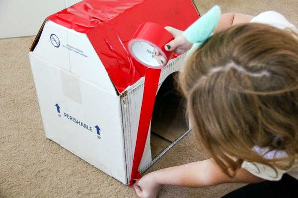 a girl covering a cardboard box in red duck tape