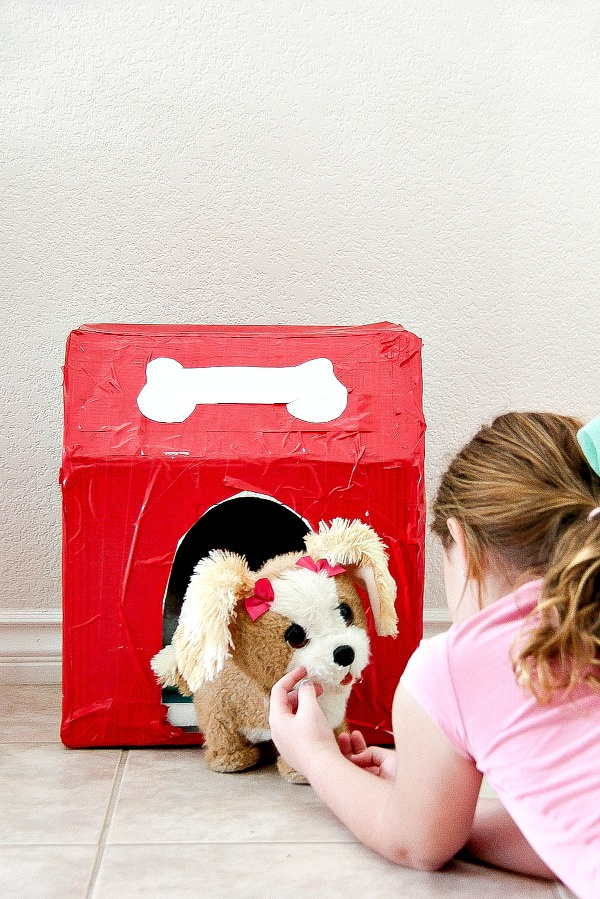 a girl playing with a toy dog in front of a cardboard and duck tape kennel she made