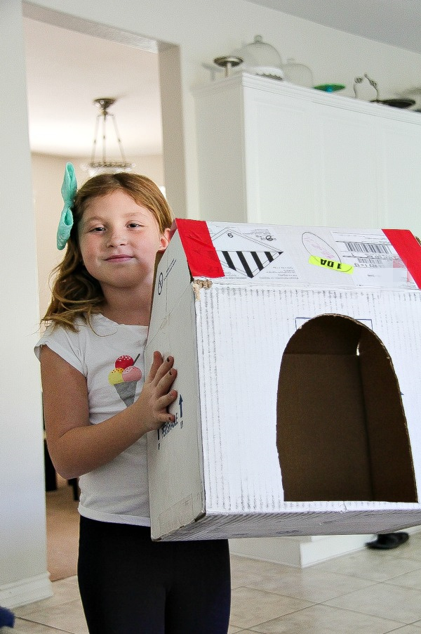 a girl making a cardboard box dog kennel