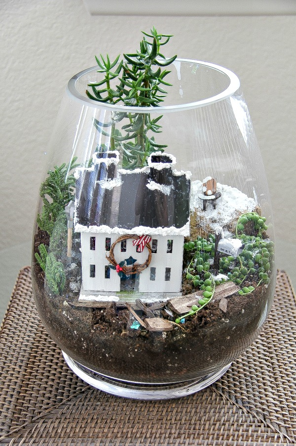 a terrarium with plants, snow, and christmas miniatures