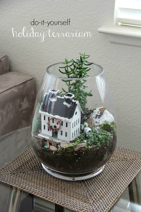 a christmas terrarium with plants, snow, and a house inside