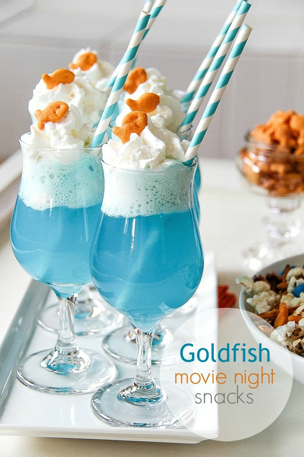 blue drinks in cocktail glasses with whipped cream and goldfish crackers