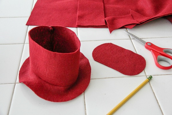 a red felt hat being made for a teddy bear