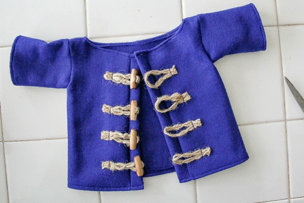 a blue felt coat handmade with rope and wood toggle closures