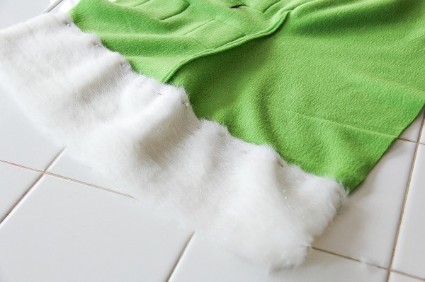 a piece of fur pinned to the top of a green fleece stocking