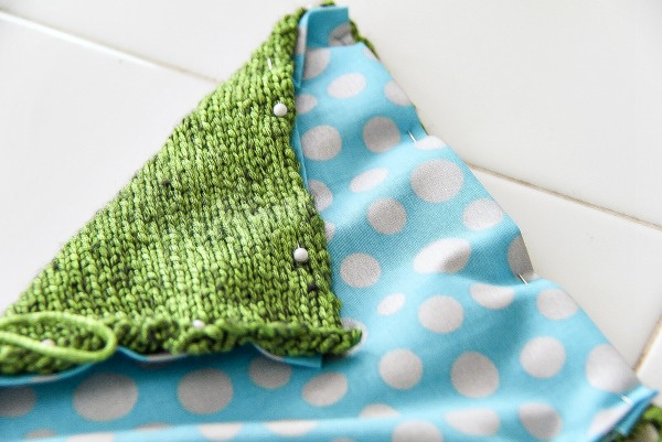 blue and white spotted fabric pinned to green knitting