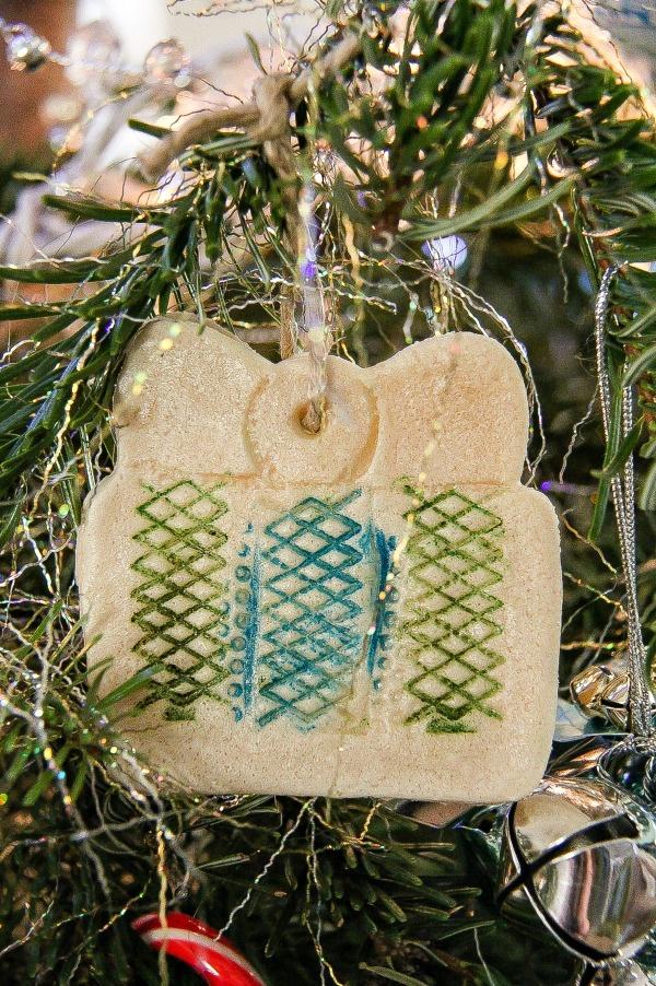 a handmade salt dough christmas present ornament hanging on a tree