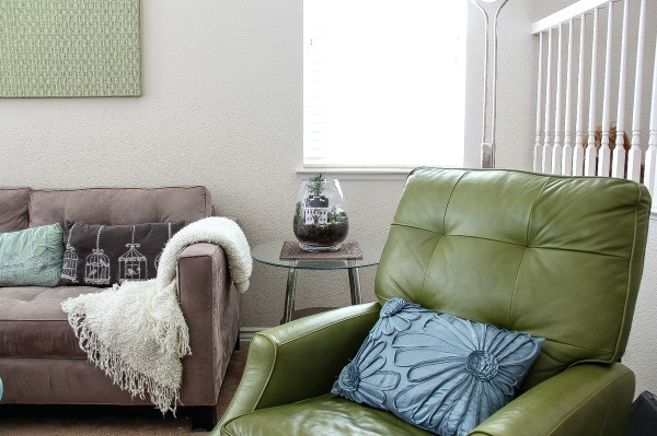 a green chair, sofa, cushions, and a christmas terrarium on a side table