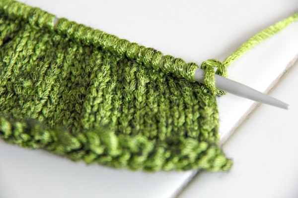 green knitting on a needle