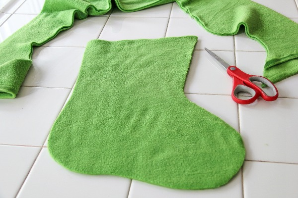 a christmas stocking being cut out of green fleece