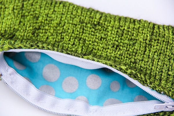 a green knit pouch with a zip and blue and white spotted fabric inside
