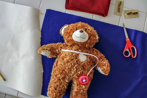 a teddy bear lying on blue felt to take measurements for making a coat
