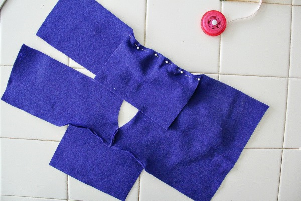 pieces of blue felt being pinned and sewn to make a coat