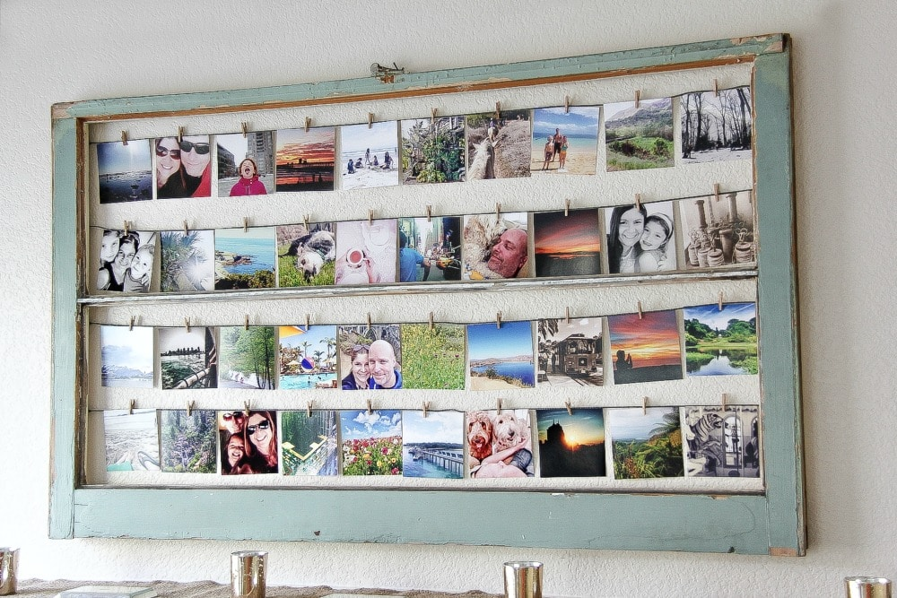 square photographs hung inside a window using wood pegs