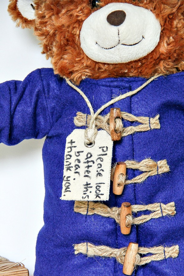 a tag hung around a bears neck that reads please look after this bear just like paddington