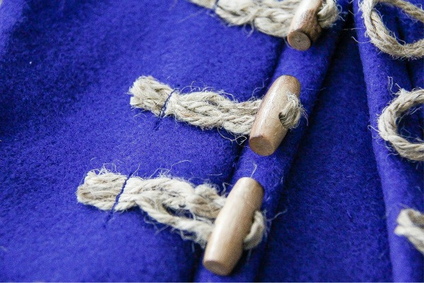 a wood toggle with rope through it sew onto blue felt to close a coat