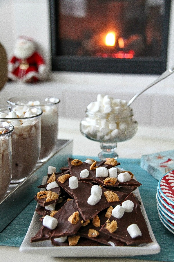 s'mores treats and hot chocolate on a table in front of a fire