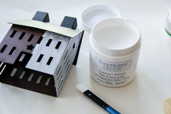a brown tin house being painted white