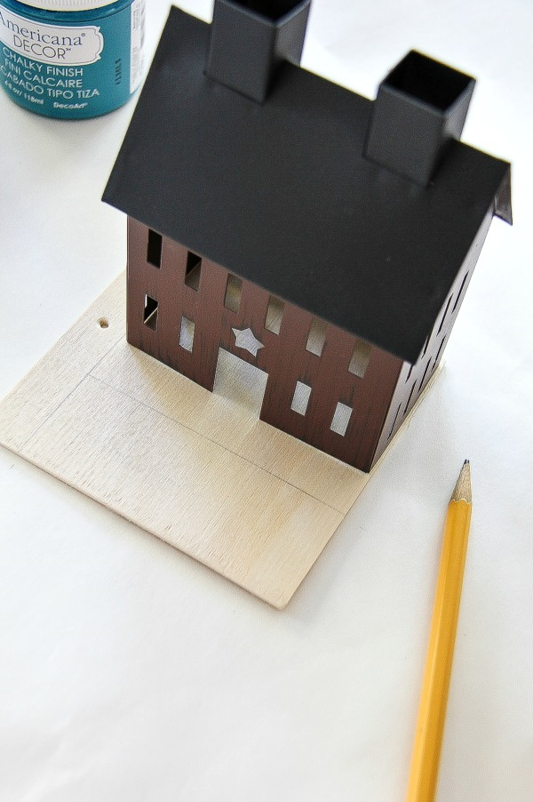 a tin house on top of a piece of plywood