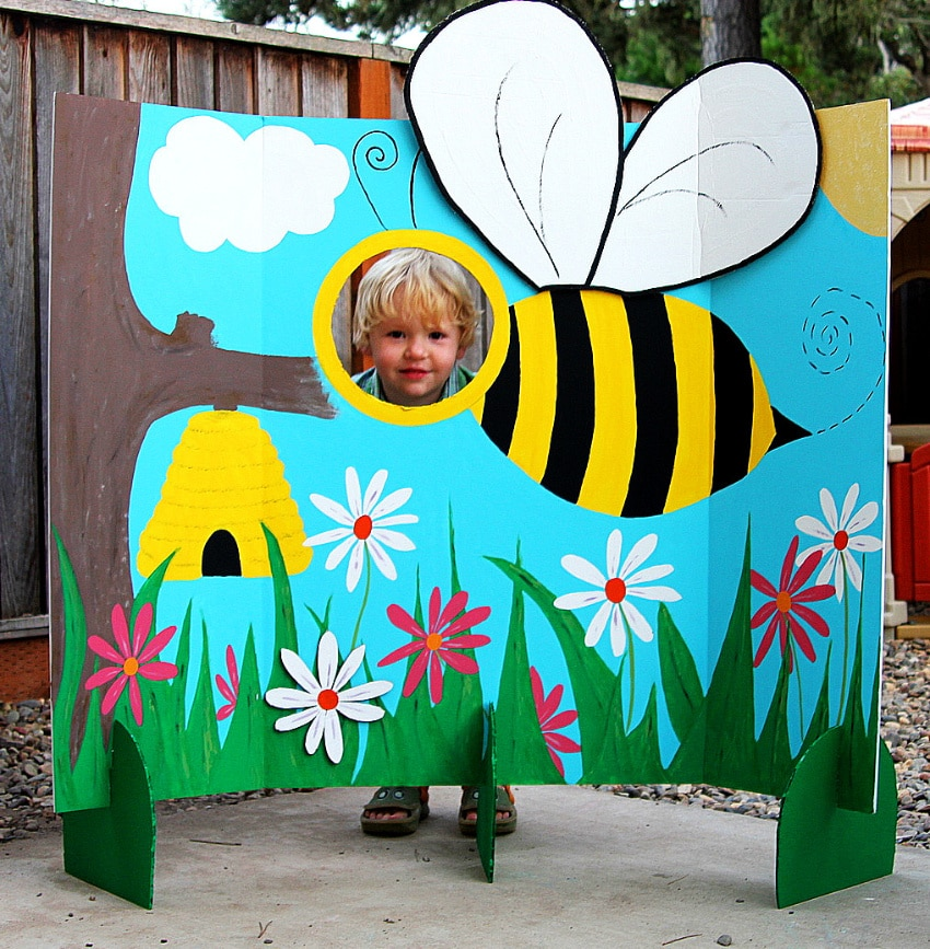 a tri-fold board painted with flowers and a giant bee with a hole cut out for photos