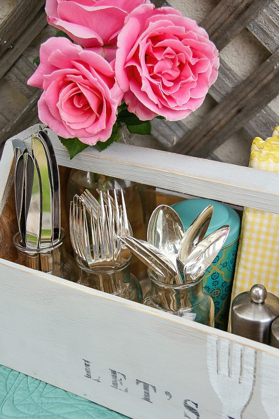 utensils in jars being stored in a grey wood vintage caddy outside