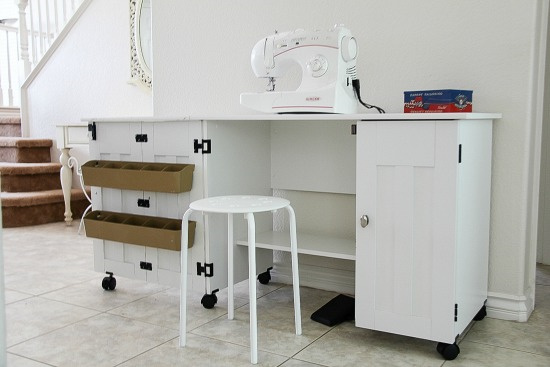 a white sewing table that can be folded down and is on wheels to move around