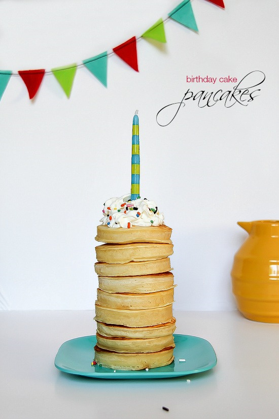 small round pancakes stacked on top of each other with whipped cream, sprinkles, and a birthday candle on top