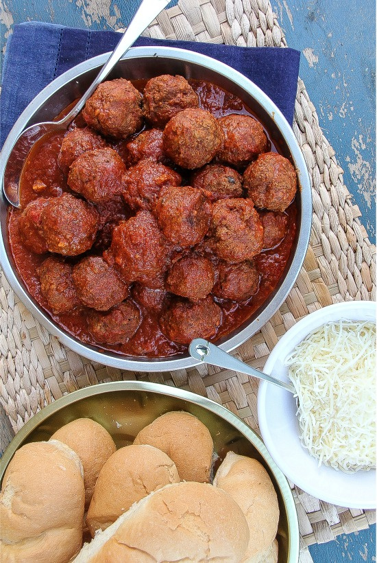 meatballs in a red sauce with hot dog buns and cheese
