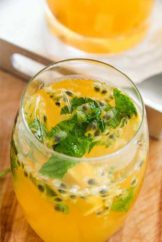 passion fruit sangria in a glass with fresh mint, ice, and passion fruit seeds
