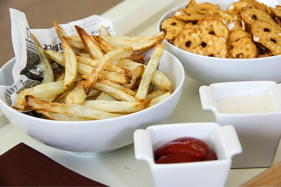 french fries and pretzels in bowls with dipping sauces