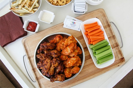 wings, fries, carrot sticks, celery, pretzels and condiments on a table