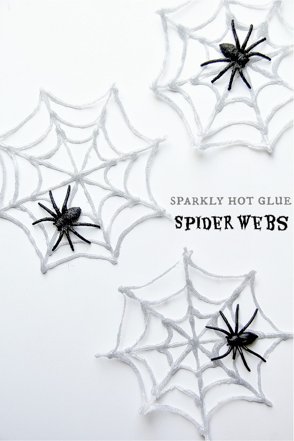 spiderwebs made of hot glue and glitter with black plastic spiders on them