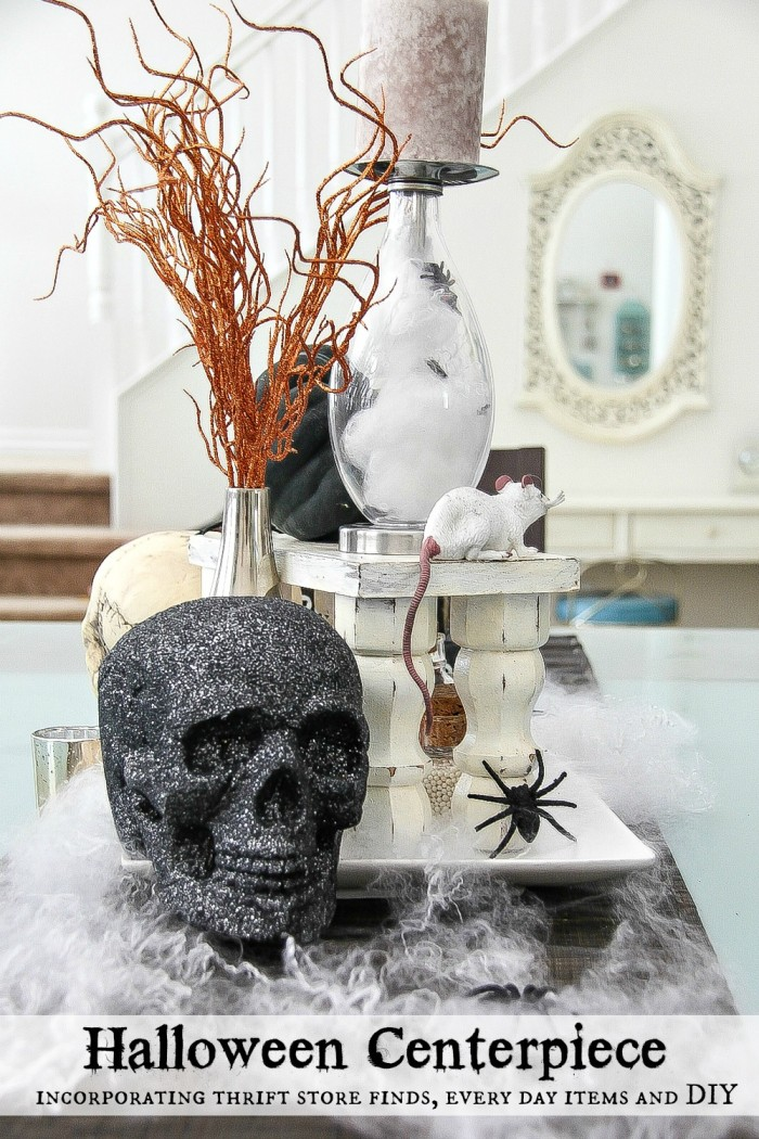 a Halloween centerpiece for a dining table with black glitter skull, candles, spider webs and more