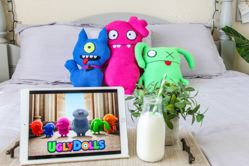 handmade ugly dolls character pillows on a bed with the movie ready to play