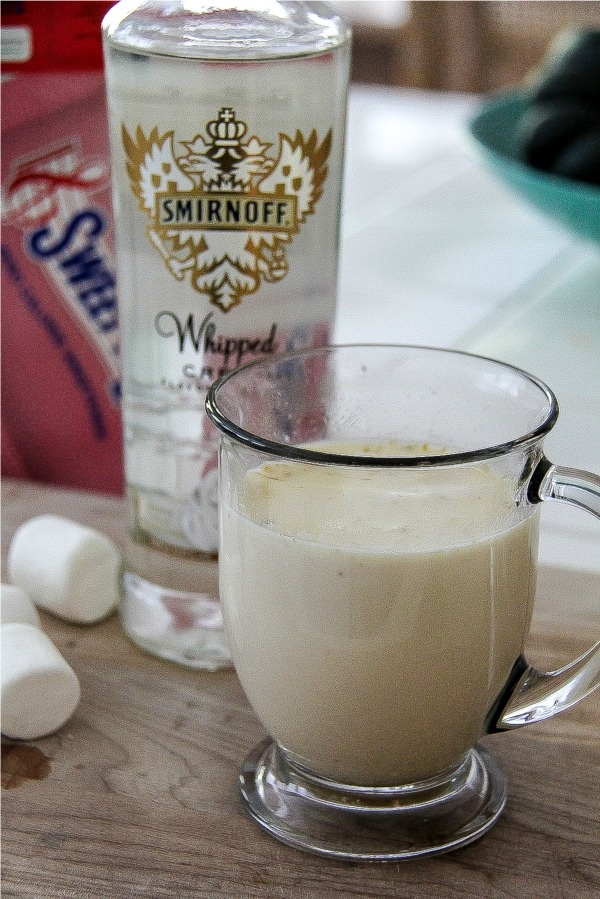 a bottle of whipped cream smirnoff vodka with a white hot chocolate