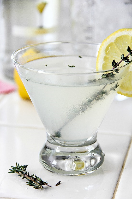 lemon drop cocktail in a glass and garnished with thyme and a lemon slice
