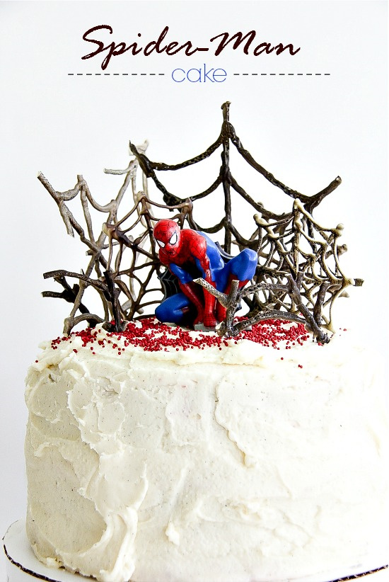 a decorate spider-man cake with webs and a toy spider-man sitting on top