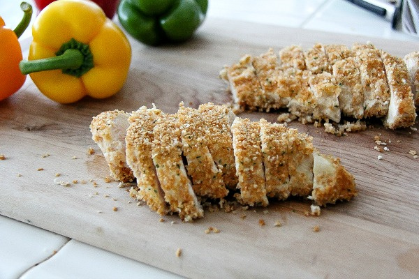 baked crumbed chicken breasts sliced into pieces on a cutting board