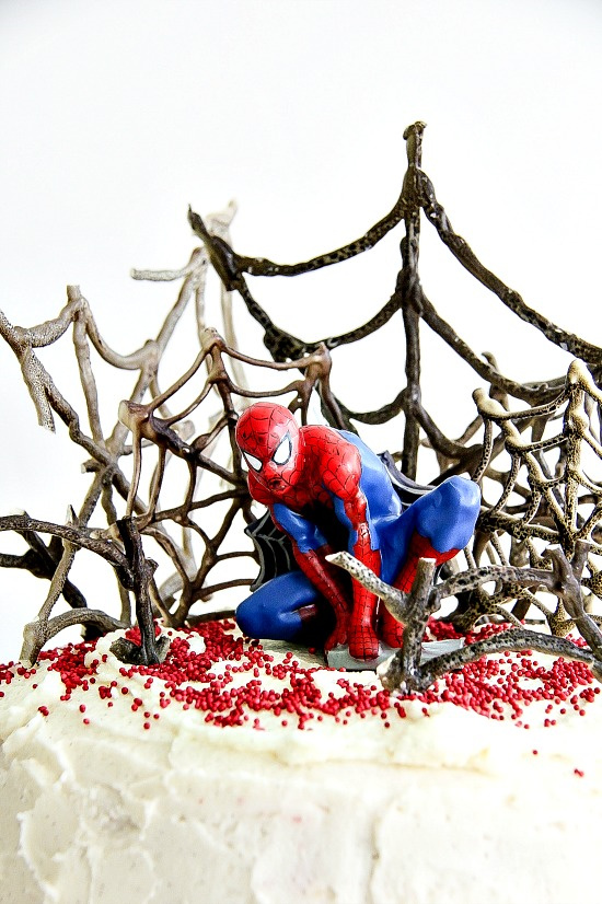 a white cake with black spiderwebs on top and a spider man doll