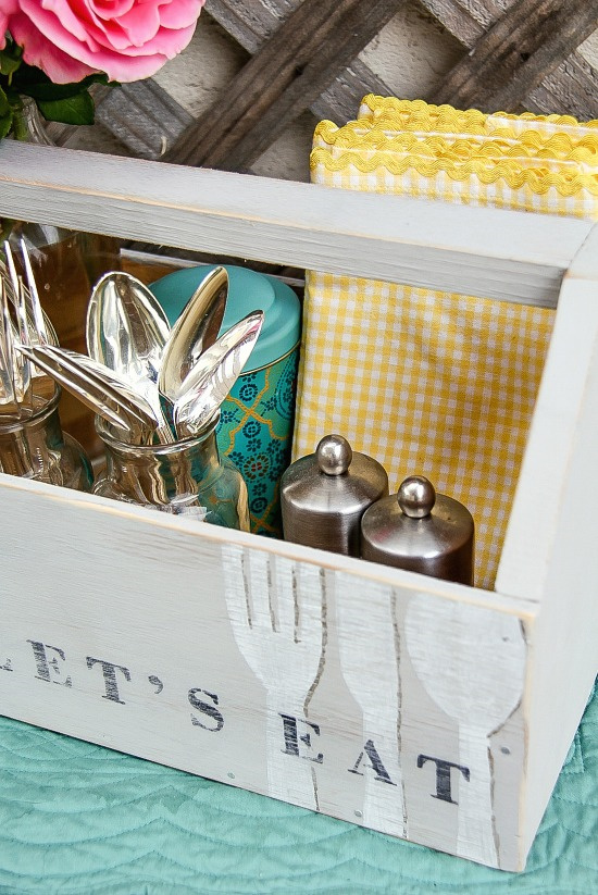 supplies for an outdoor party inside a vintage grey wood caddy