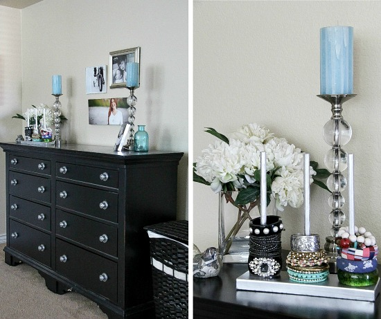 a black chest drawers topped with candle sticks, photo frames and jewelry