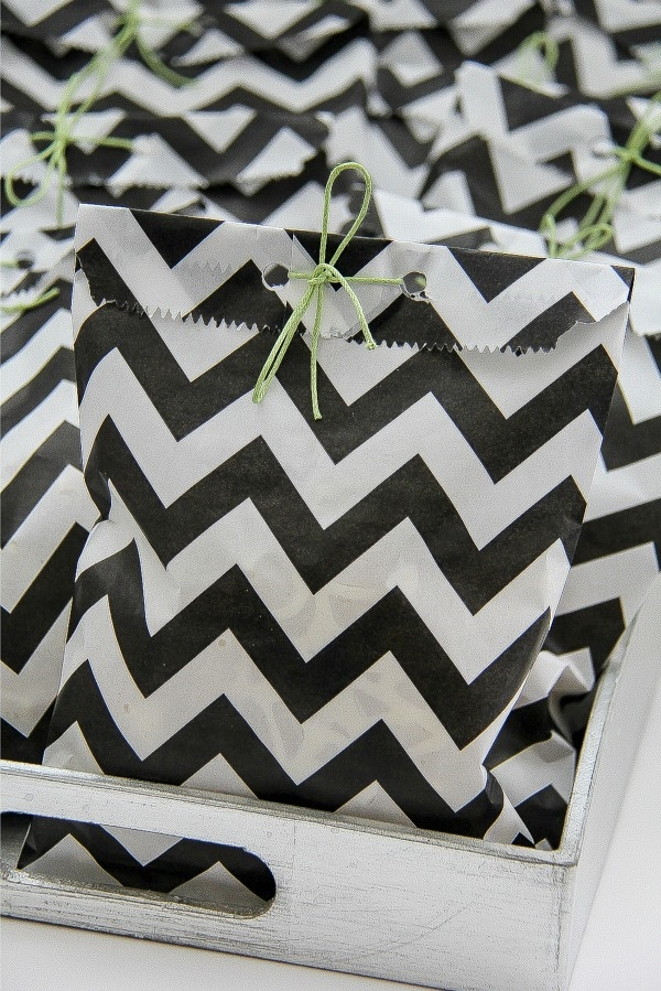 black and white party treat bags tied with green ribbon