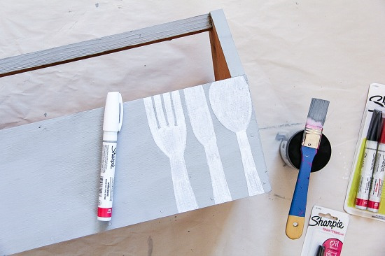 wood caddy with utensils being painted on it