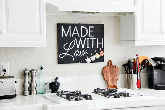 made with love chalkboard kitchen sign in a white and black kitchen