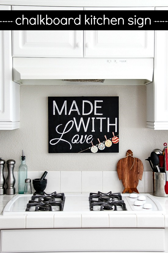 chalkboard kitchen sign hanging above the stove in a white kitchen