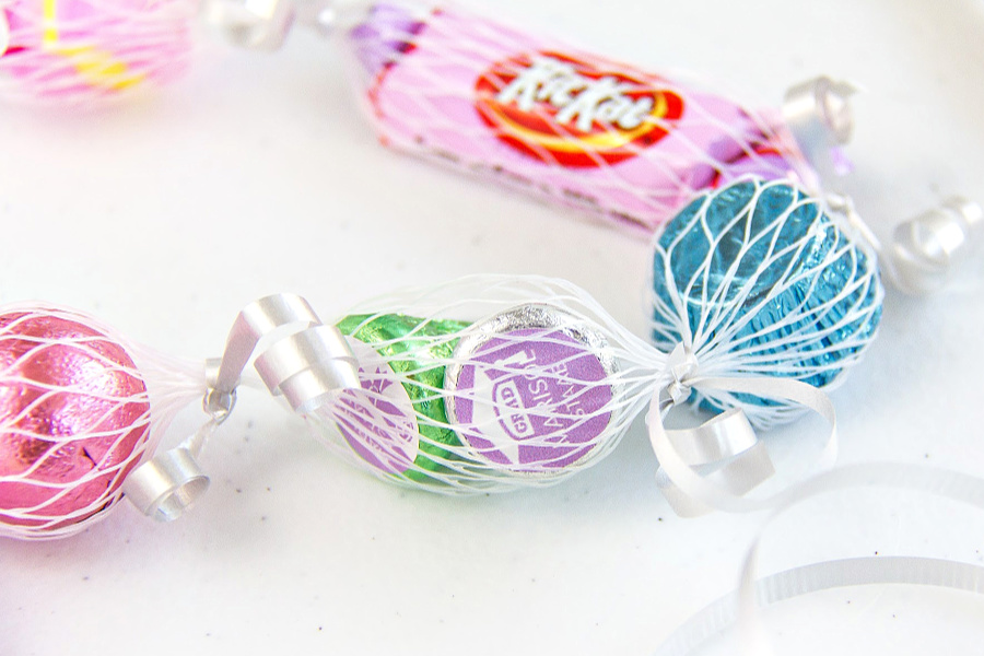 candy in a net sleeve tied with curling ribbon to make a lei