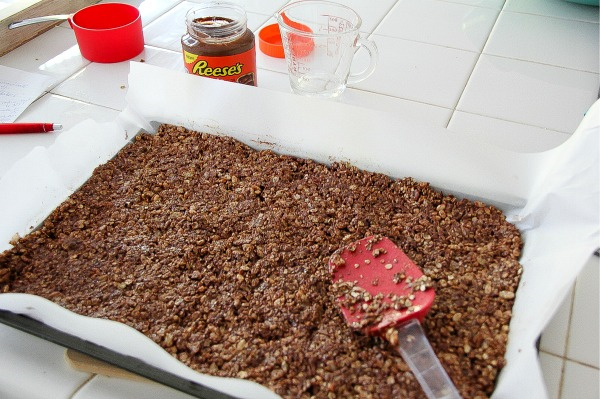oats and chocolate being spread on a baking tray lined with parchment paper