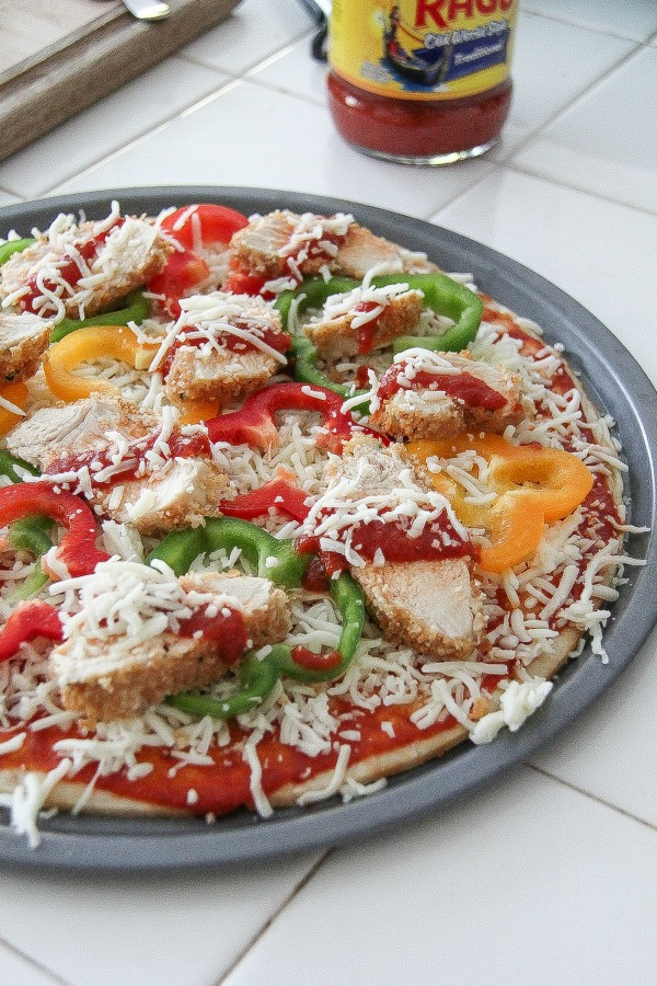 a pizza base topped with baked chicken, bell peppers and cheese