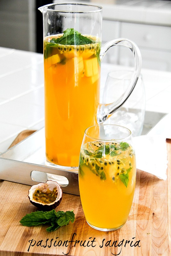 passion fruit sangria in a glass pitcher and a glass with ice