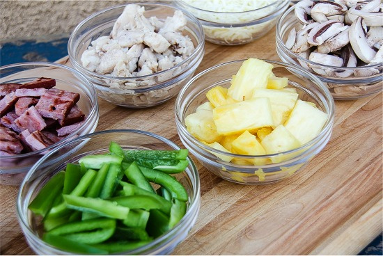 individual bowls filled with pizza toppings such as green peppers, pineapple, grilled ham, mushrooms, and chicken.
